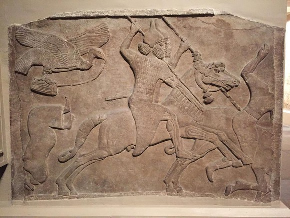 Relief of Assyrian soldier in battle on horse and bird carrying remains of enemy