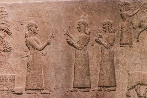 Relief of Assyrians taking notes of plunder after battle