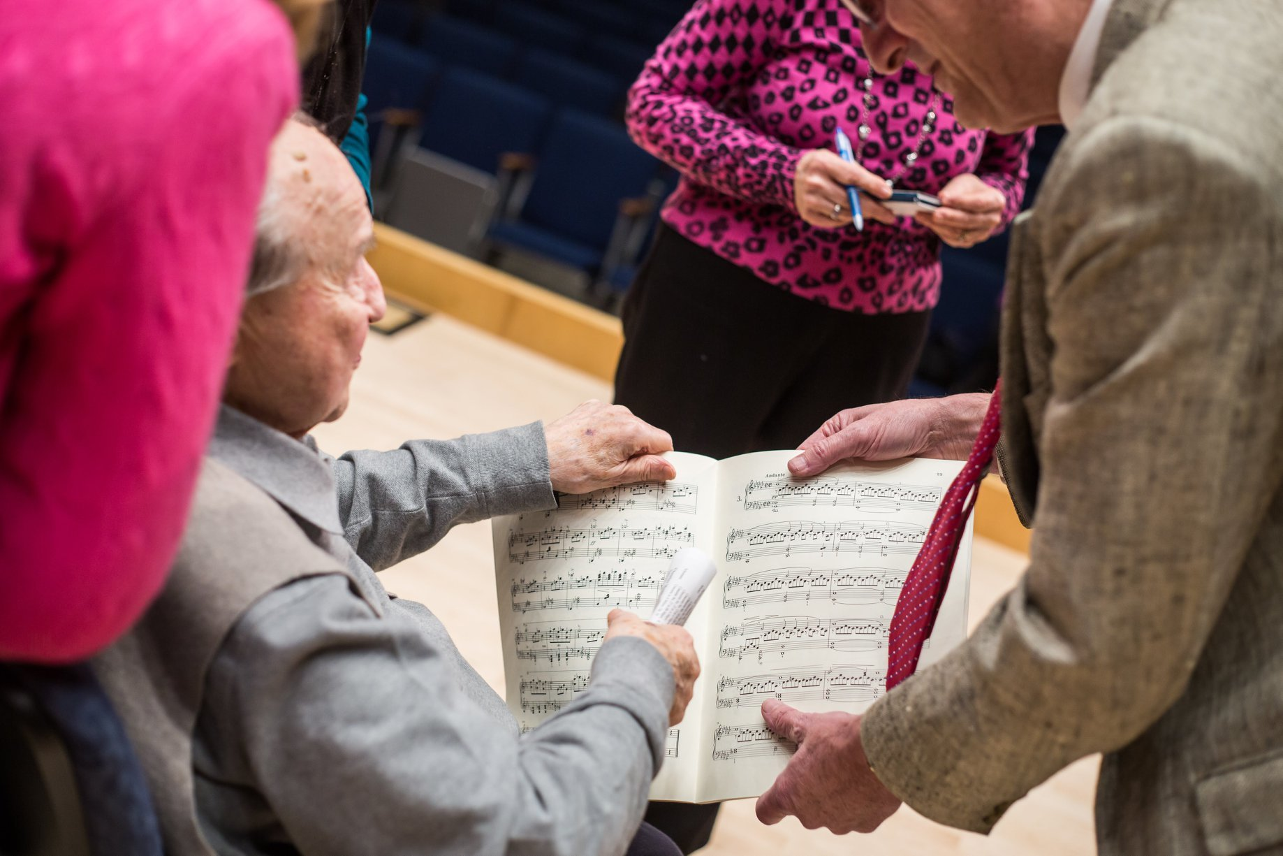 Pressler looking at sheet music with faculty members and students.