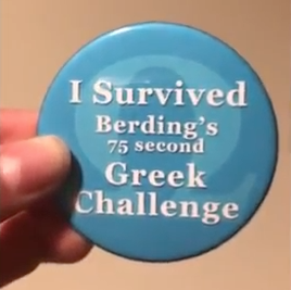 "Person holding button that reads: ""I SURVIVED BERDING'S 75 SECOND GREEK CHALLENGE"""