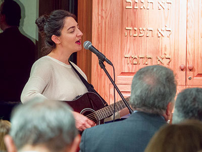 Woman leading worship at the Feinberg Center in Brooklyn