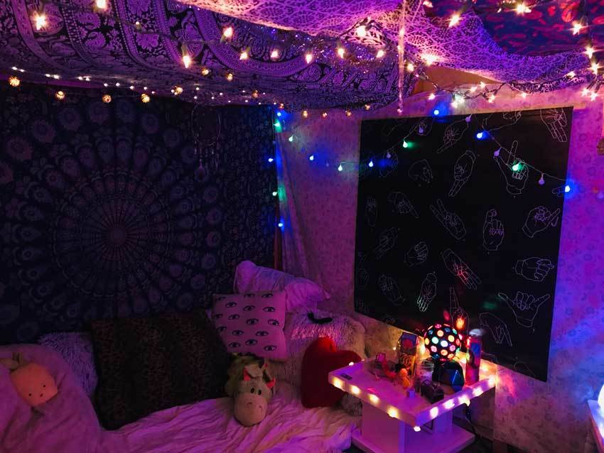 The space under a lofted bed features twinkle lights, patterned cloth, and a cozy area with a stuffed donkey.