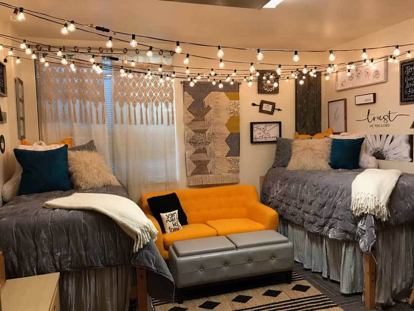 String lights cross the entire room and a bright orange couch contrasts with the gray and neutral bedding.