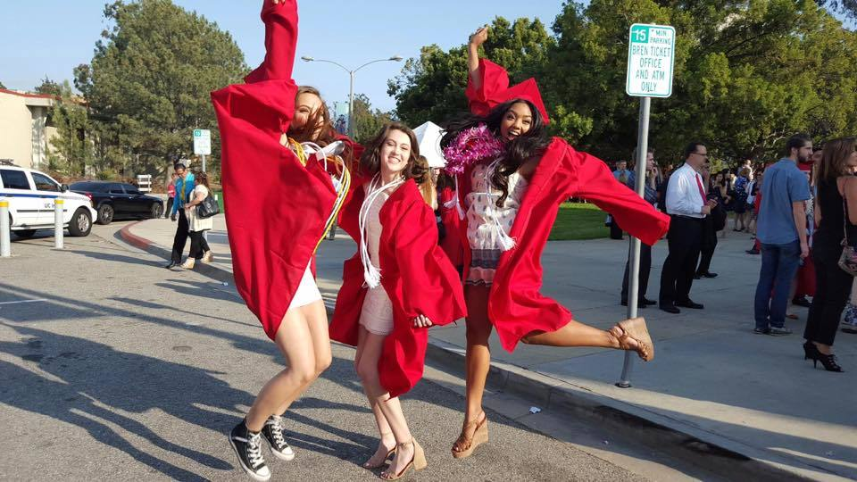 Aubrey and friends jumping at graduation in cap and gown