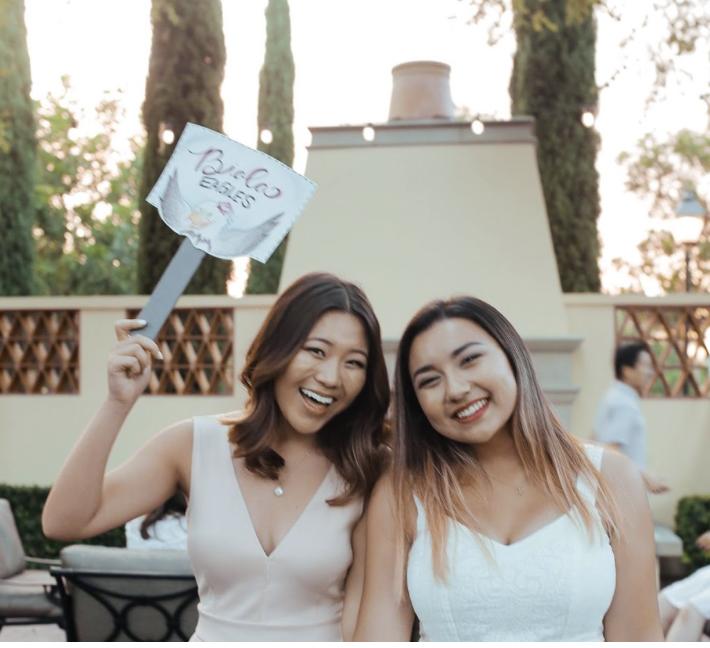 Meagan and friend waving 'Biola Eagle' sign