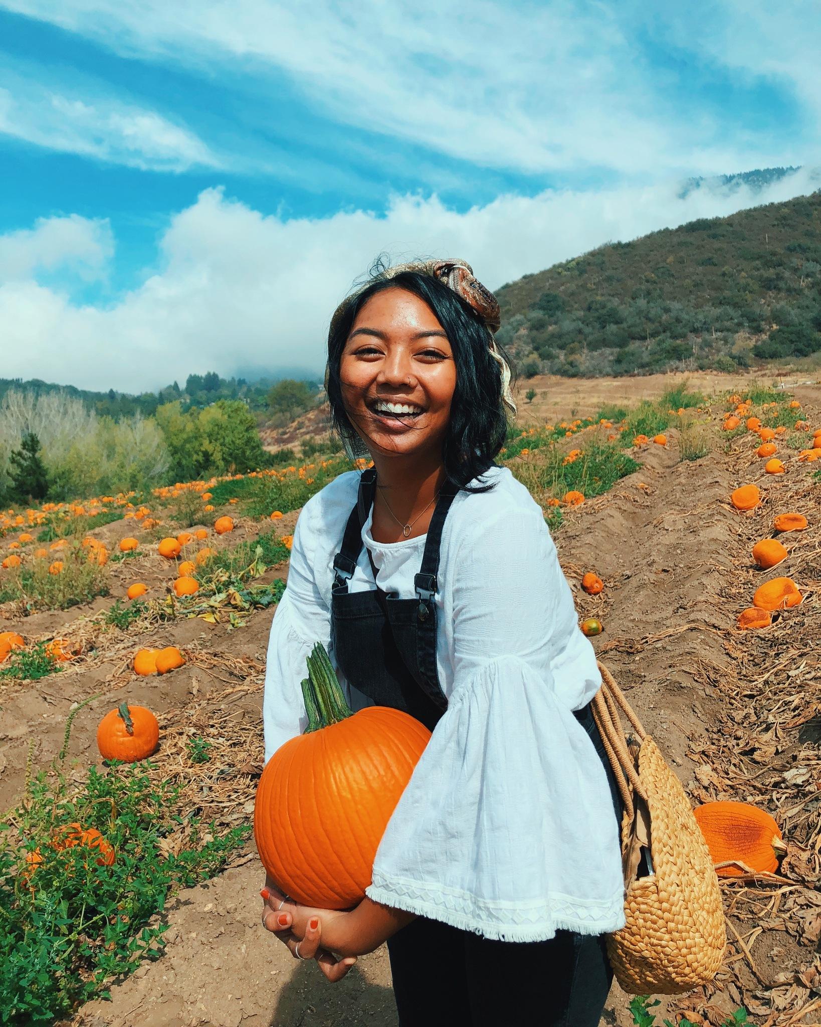 Photo of Aubrey holding a pumpkin at Riley's Apple Farm