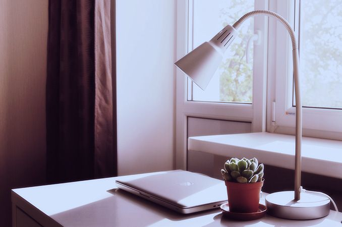 a bright desk with a lamp, a plant and a laptop