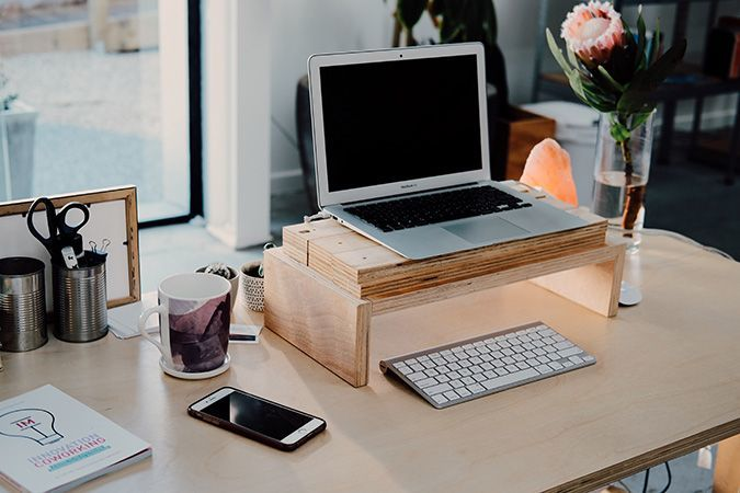 A desk with a laptop elevated on a wooden stand