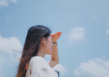 A woman shields her eyes from the sun while looking into the distance