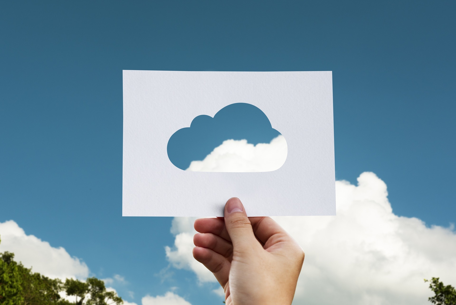 A hand holds a paper up to the sky with a cloud shape cut out.