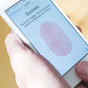 A smartphone displays a thumbprint on the screen for Touch ID.