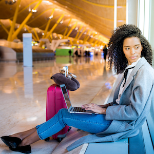 "A woman with a laptop sits in an airport. ""Stay protected while connected. Public Wi-Fi is not secure and can put your device and data at risk."""