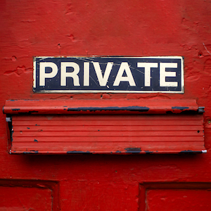"A mail delivery slot in a red door has a sign above it that says, ""Private."""
