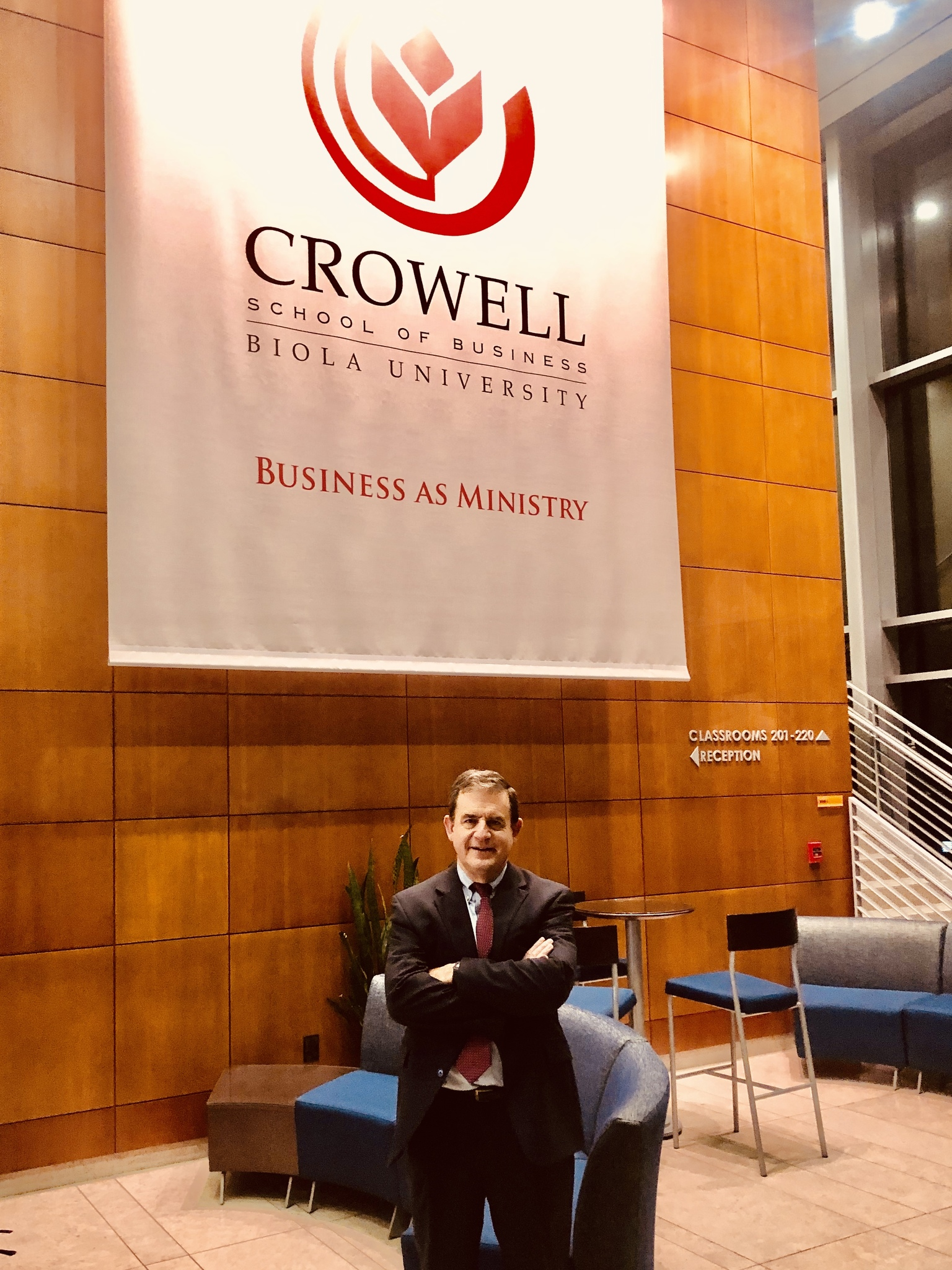 Bob Doll in front of Crowell lobby banner