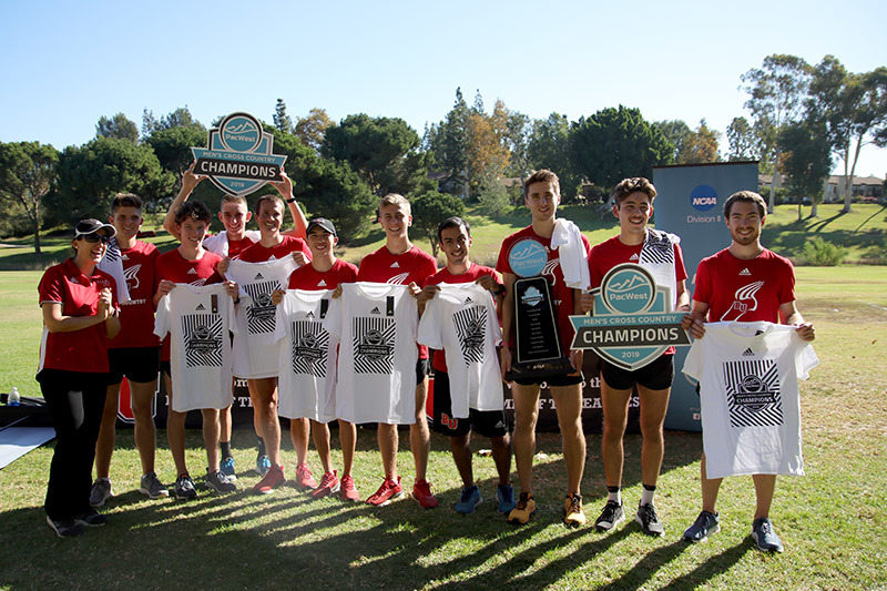 Photo of Men's Cross Country team holding two championship plaques and T-shirts