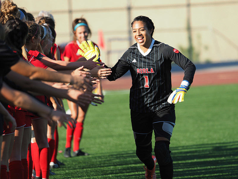 Photo of Biola goalkeeper giving high-fives to her teammates