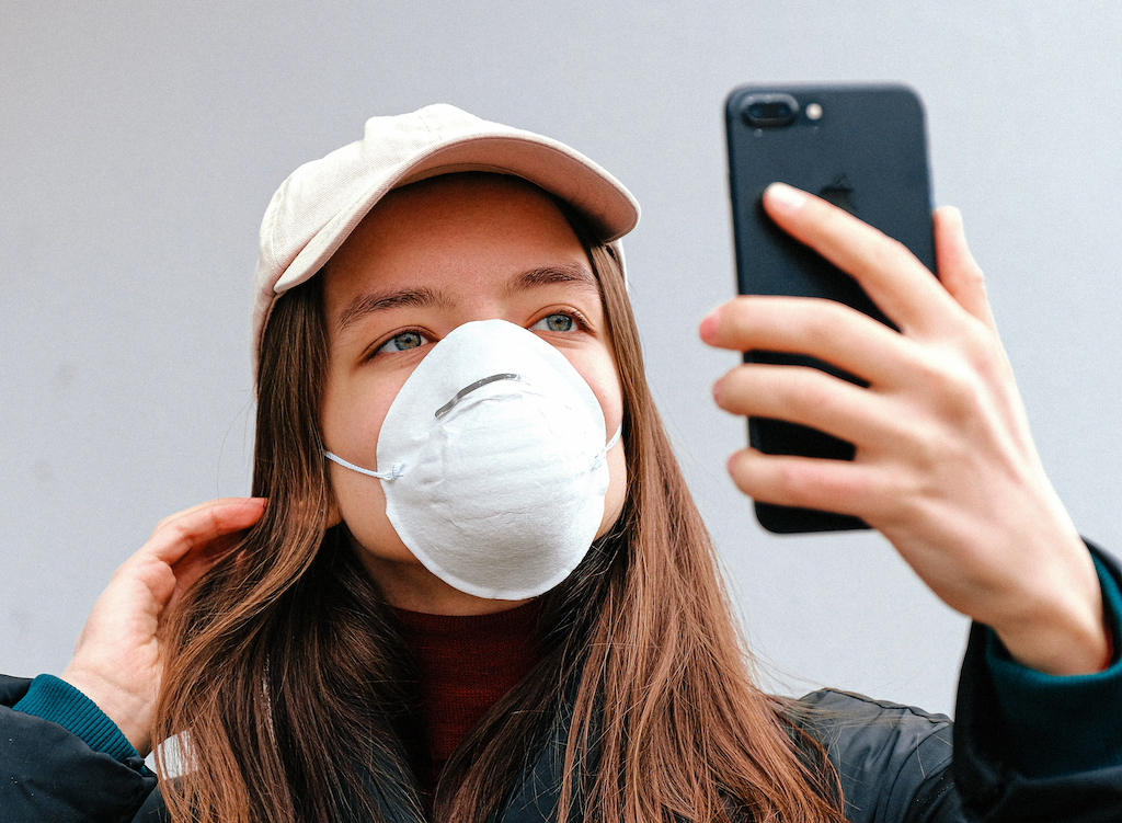 A woman with a dust mask looks at her upheld smartphone as if taking a selfie.