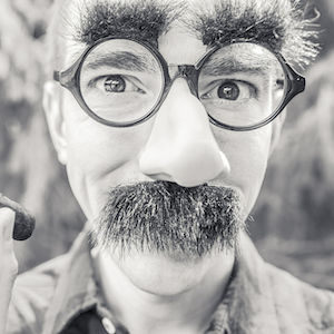 A man wears a disguise of glasses, false nose, and mustache.