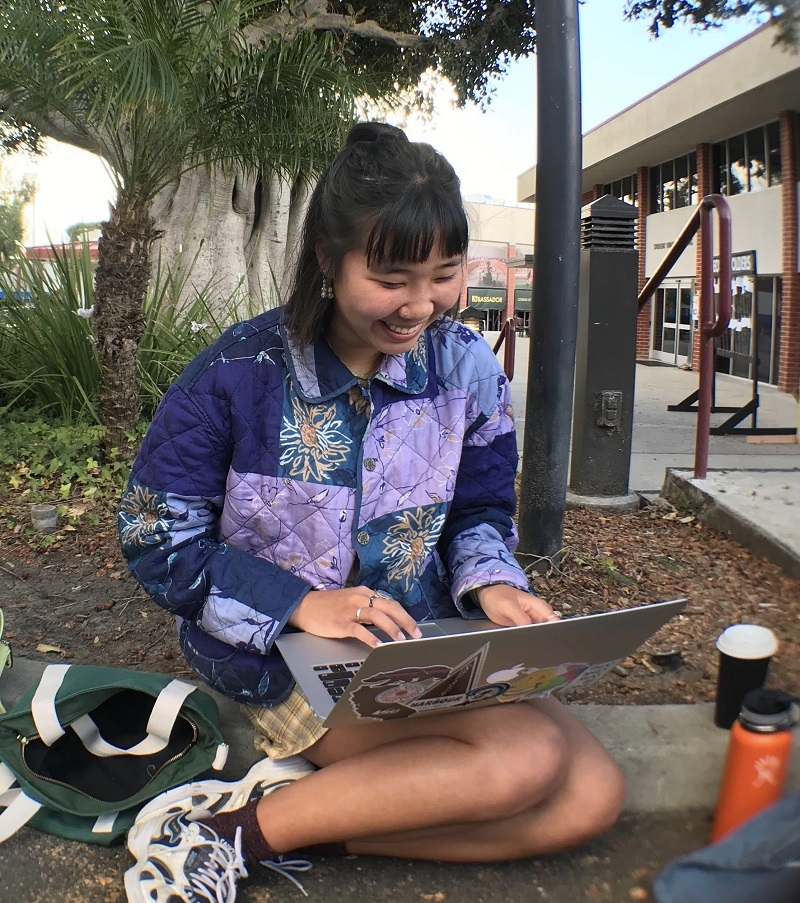 Kristen sitting on the curb of Biola's campus next to the Fireplace Pavilion, waiting in line for Missions Conference. She is wearing a celestial-themed puffy jacket, many rings and at present typing on her laptop
