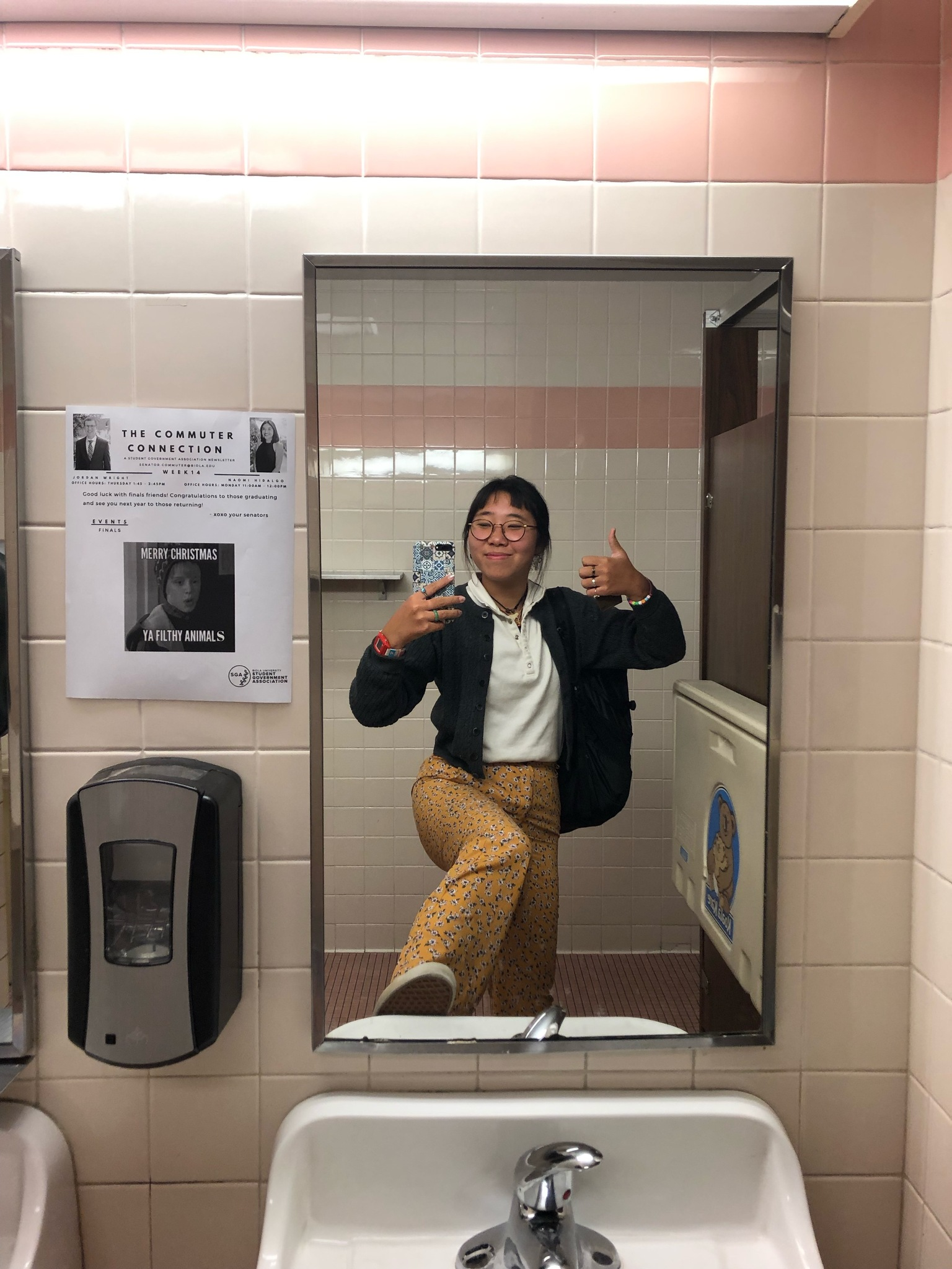 Kristen takes a selfie in one of the campus bathrooms, there's a poster to the side of the mirror detailing a Merry Christmas message for Commuters to campus