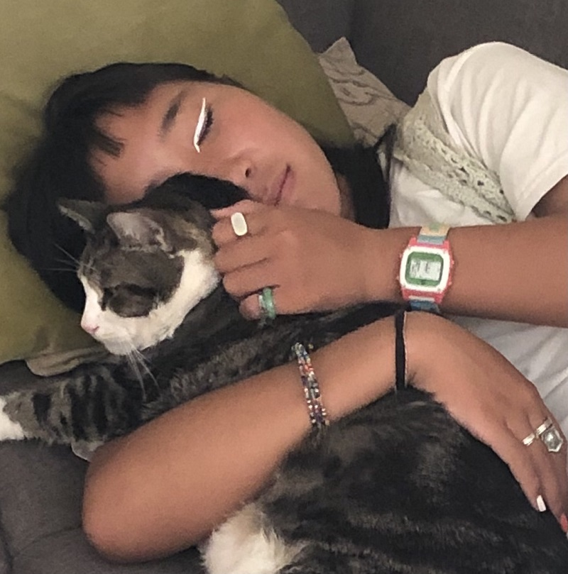 Kristen snuggling with her cat, a moment that brings her joy in her long days