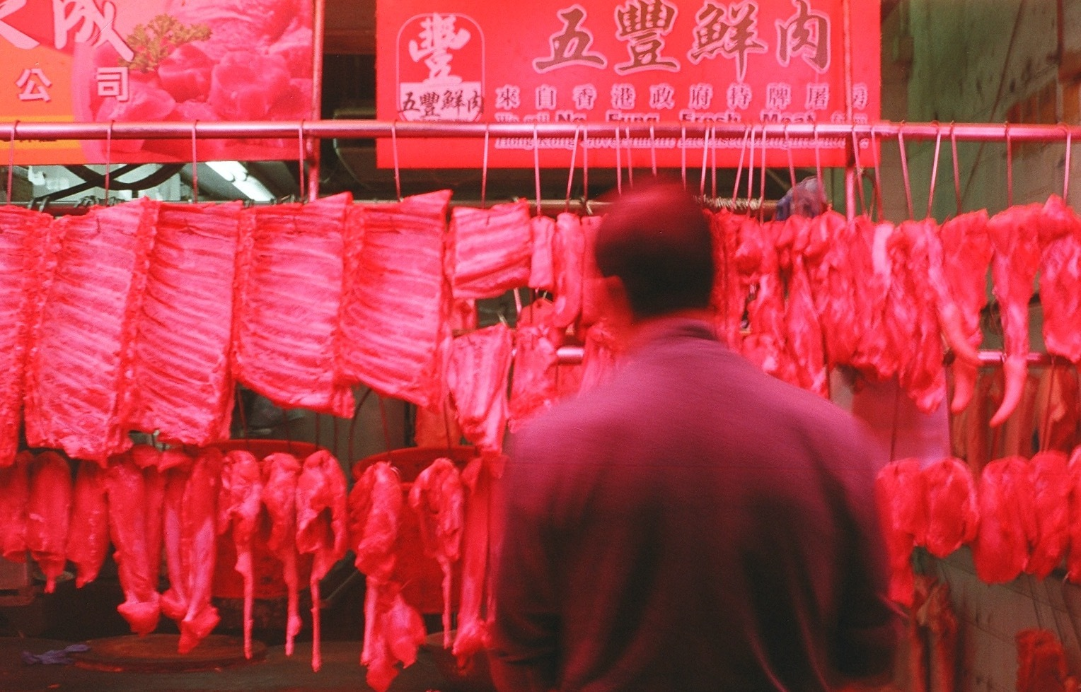 A film photo I captured in Hong Kong and included in my portfolio. It is of a man looking at hanging pieces of meat.