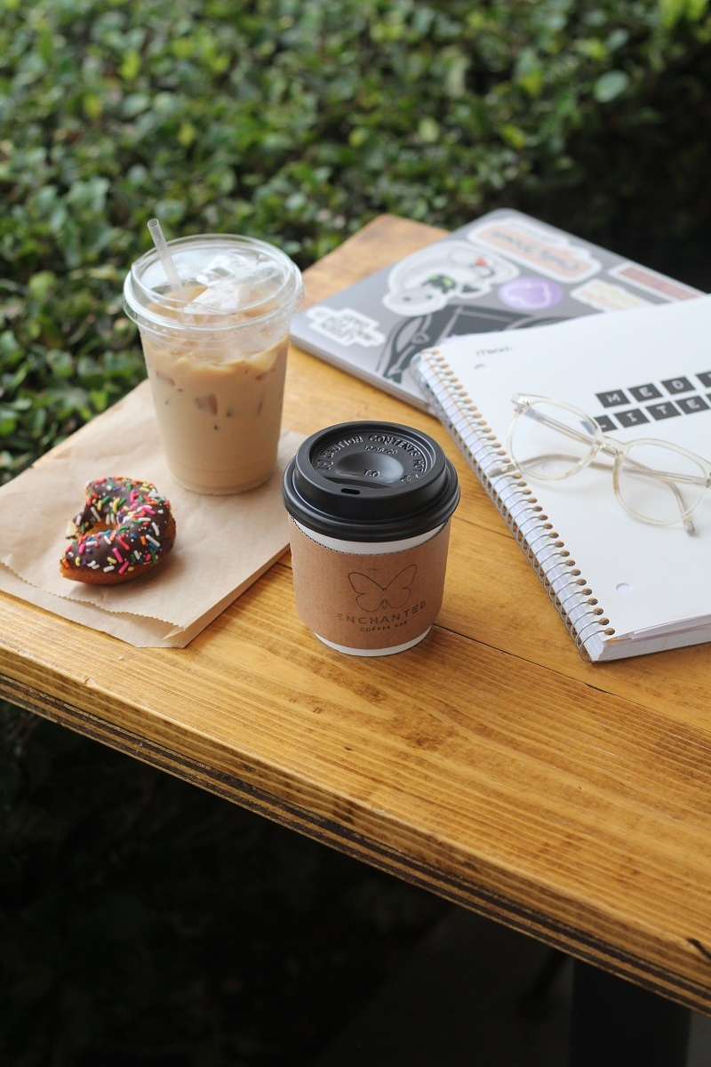 A table with two cups of coffee, a chocolate donut with sprinkles, and