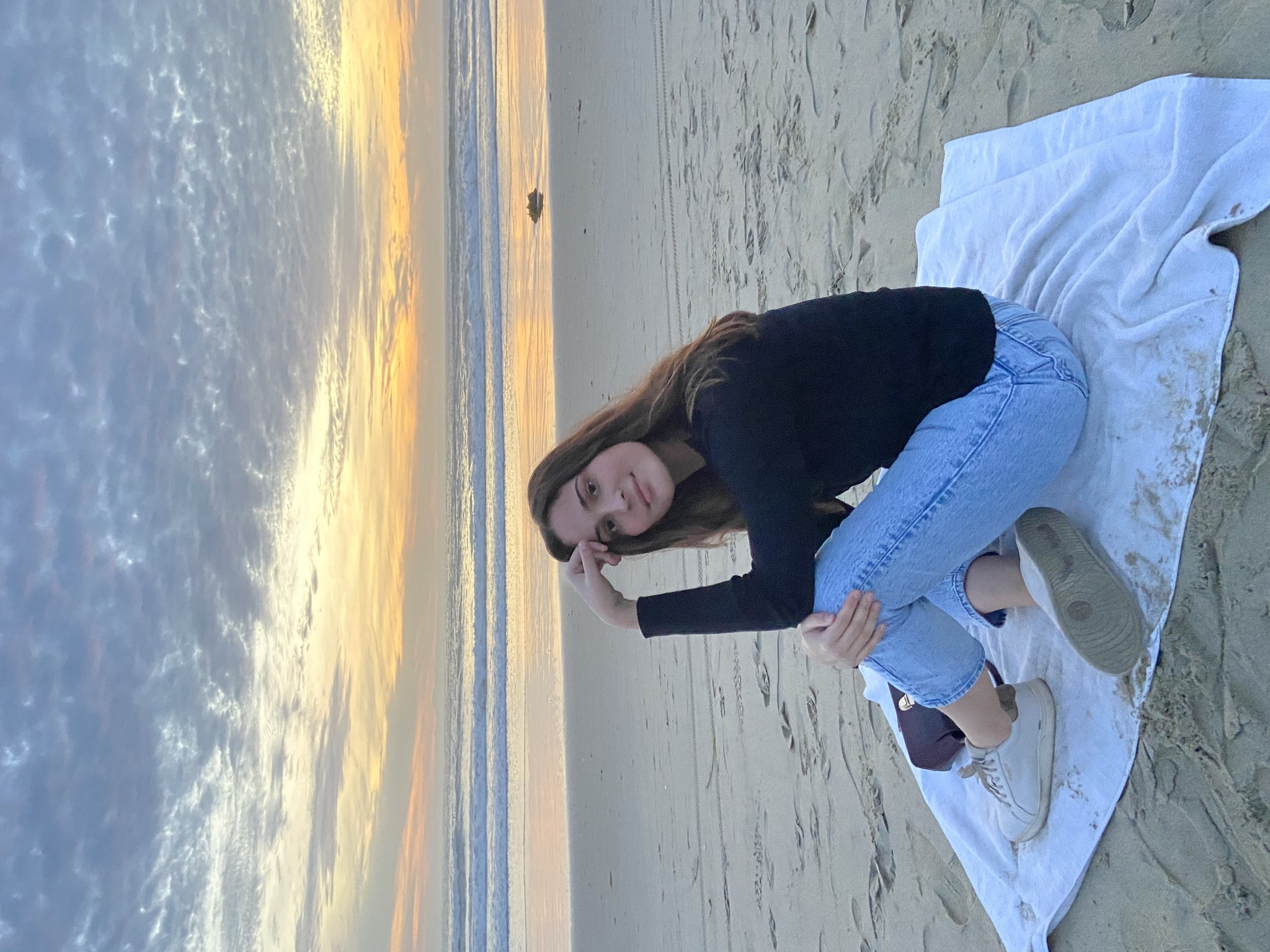 Maggie sitting on a white towel at the beach during sunset