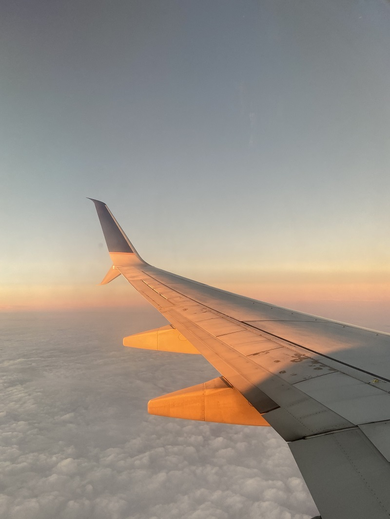 Looking outside a plane window at sunset
