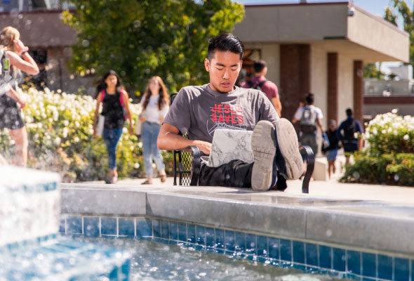student using a laptop next to a fountain