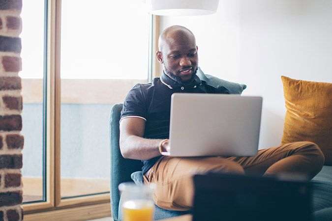 A man sitting by a window works on his laptop