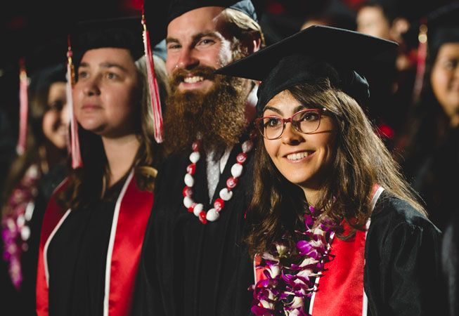 Students at commencement in caps and gowns with leis