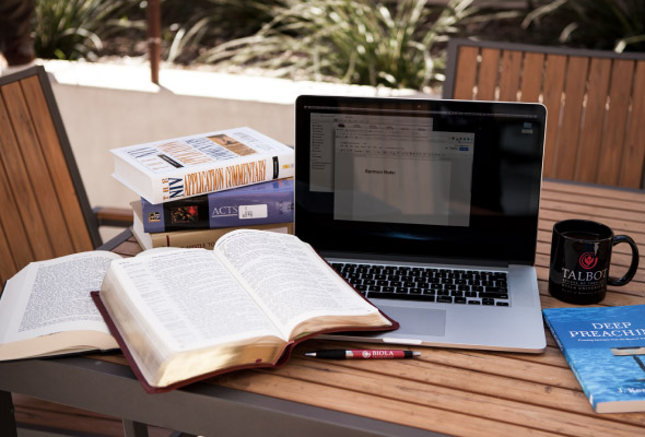 A laptop, books, bible, and mug sit on an outdoor table