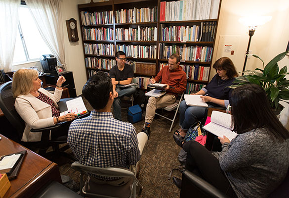 A group of students and faculty sit in a circle in an office, discussing and taking notes