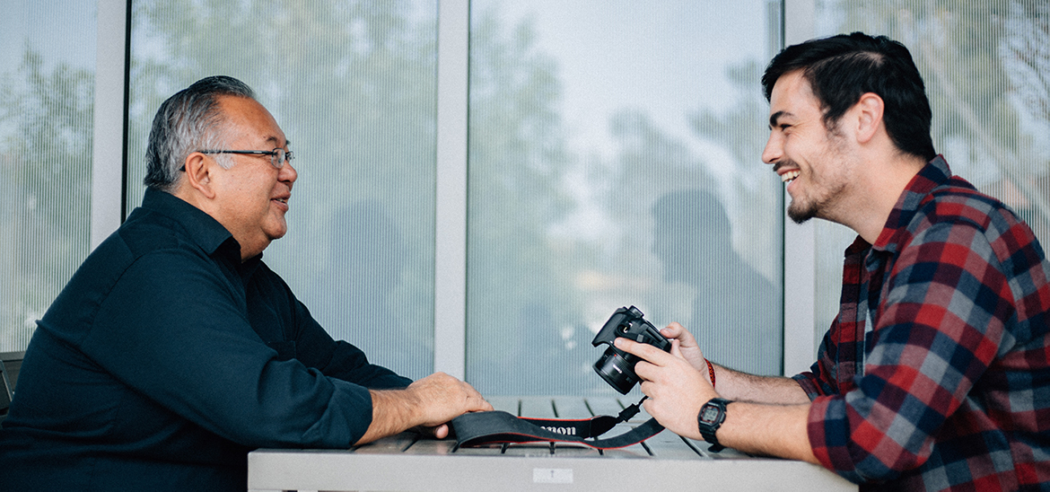Professor and student holding a camera interacting