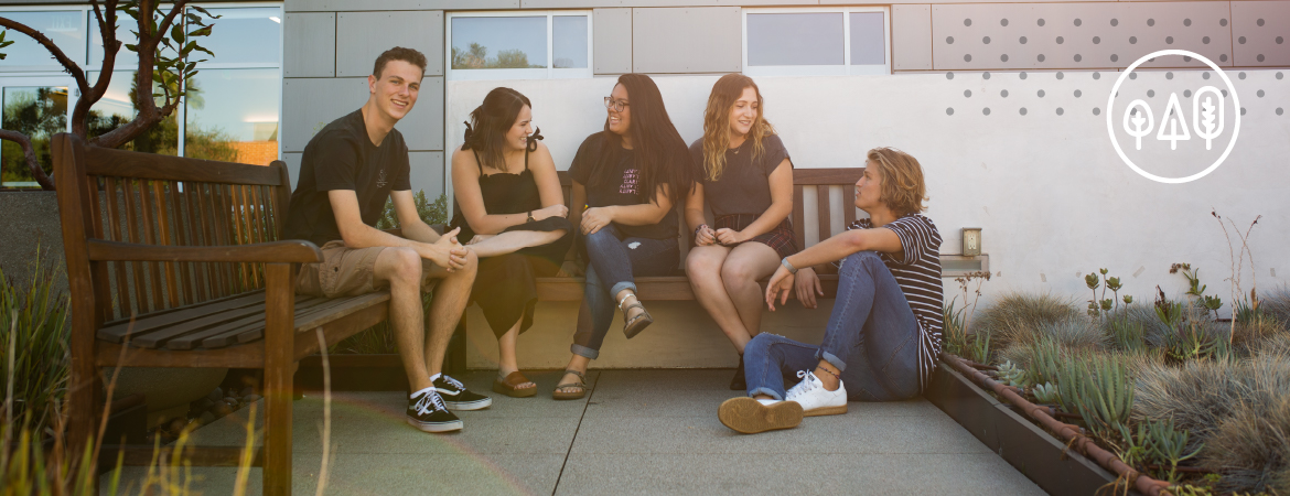 A group of students talking and laughing on a bench