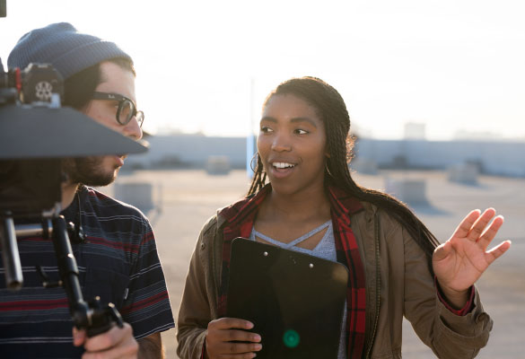 A young woman with a clipboard talks to a young man with a video camera
