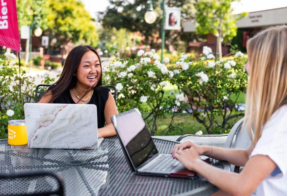 Two students talking and using laptops outside